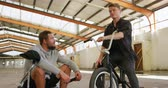 concentrando : Front view of two young adult Caucasian men sitting on BMX bikes talking to each other in an abandoned warehouse