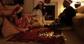 three two one : Side view of a mixed race family sitting on the floor with their young daughter in their sitting room at christmas, wearing santa hats, smiling, with dad playing guitar and singing, and the girl playing with fairy lights