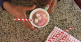 кондитерские изделия : High angle close up view of a young mixed race girl in the kitchen at Christmas, stirring a mug of hot chocolate and marshmallows with a straw and taking a sip