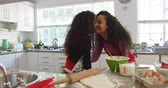 biscoitos : Side view of a mixed race mother  in a kitchen with her young daughter at christmas making cookies, smiling, facing each other and touching noses