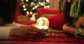 frohe weihnachten : Side view close up of a mixed race mother with her young daughter in their sitting room at christmas, lying on the floor facing each other looking at a snow globe between them and smiling to each other Stock Footage