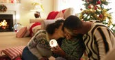 three two one : Front view of a mixed race familywith their young daughter in their sitting room at christmas, sitting together on the floor with their daughter between them, both kissing her, smiling and looking at a snow globe she is holding
