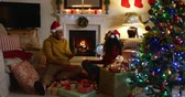 frohe weihnachten : Side view of a mixed race couple in their sitting room at Christmas, wearing santa hats and sitting together on the floor, the man receiving a present from the woman, both laughing and then embracing