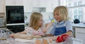 pim : Front view of young Caucasian brother and sister in their kitchen at Christmas time making cookies, rolling dough with a rolling pin together, the girl putting flour on the face of her brother Stok Video