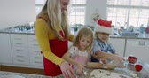 fresa : Side view of a happy young Caucasian mother with her young daughter and son in their kitchen at Christmas time making cookies, having fun using cookie cutters to cut shapes in rolled dough, the son is wearing a Santa hat
