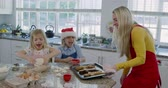 fresa : Side view of a happy young Caucasian mother with her young daughter and son in their kitchen at Christmas time making cookies, the son is wearing a Santa hat and both siblings are jumping with excitement as mum brings baked cookies from the oven on a baki