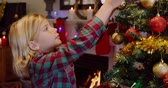 украшение : Side view of a young Caucasian boy decorating the Christmas tree in his sitting room with baubles at Christmas time