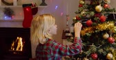 자유 시간 : Side view of a young Caucasian boy decorating the Christmas tree in his sitting room with baubles at Christmas time