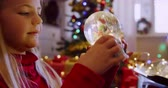 wróżka : Side view close up of a young Caucasian girl holding and shaking a snow globe in the sitting room at Christmas time and looking at it, a decorated Christmas tree in the background Wideo