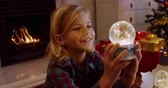 secouer : Side view close of a smiling young Caucasian boy holding a snow globe in the sitting room at Christmas time and looking at it, a decorated Christmas tree and open fire in the background Vidéos Libres De Droits