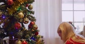cicili bicili : Side view of a young Caucasian girl decorating the Christmas tree in her sitting room with baubles at Christmas time Stok Video