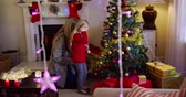 ティンセル : Side view of a young Caucasian woman and her young daughter decorating the Christmas tree together in their sitting room at Christmas time, with glowing Christmas lights hanging in the foreground 動画素材