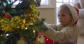 украшение : Side view of a smiling young Caucasian girl wearing a Santa hat decorating the Christmas tree in her sitting room