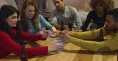 резервный : Front view of a group of five young multi-ethnic male and female friends sitting around a table building a house of playing cards and drinking bottles of beer in the sitting room of an apartment at night Стоковые видеозаписи