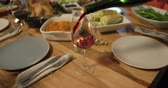 wijnen : Side view of a glass of red wine being poured from a bottle at a table at home set for Thanksgiving dinner Stockvideo