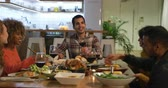 kırmızı şarap : Front view of a group of young adult multi-ethnic male and female friends sitting around a table talking and serving each other Thanksgiving dinner at home and making a toast with glasses of red wine Stok Video