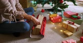 оберточной бумаги : High angle view of a mixed race woman in her sitting room at Christmas, sitting on a floor and wrapping presents Стоковые видеозаписи