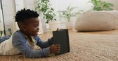 ラグ : Side view of a smiling young African American boy at home lying on the floor in his sitting room reading a book and smiling 動画素材
