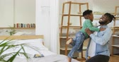 raszta : Side view of a young African American boy standing on a bed at home and jumping into the arms of his millennial father Stock mozgókép