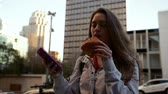 kabelka : Front view of a young Caucasian woman with long dark hair standing on a sunny city street using a smartphone and eating a pastry, slow motion Dostupné videozáznamy