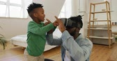 vr glasses : Side view of a young African American boy helping his millennial father use a VR headset in a bedroom at home, slow motion