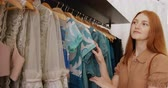 kleerhanger : Side view close up of a young Caucasian woman with long red hair looking at dresses hanging on a clothes rail in a fashionable clothes shop, slow motion