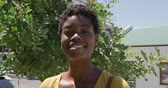 トレンディー : Portrait close up of a young African American woman with short hair standing in a sunny city street smiling to camera with trees behind her, slow motion