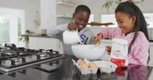 krug : Front view of a smiling young African American brother and sister at home in the kitchen making pancakes, adding the ingredients into a mixing bowl, the boy pouring milk and the girl stirring, slow motion