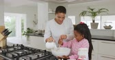 krug : Front view of a smiling African American woman and her young daughter at home in the kitchen making pancakes, adding the ingredients into a mixing bowl, the mother pouring milk and the girl stirring, slow motion Videos
