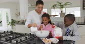krug : Front view of a smiling African American woman and her young son and daughter at home in the kitchen making pancakes, adding the ingredients into a mixing bowl, the mother pouring milk, the boy adding flour and the girl stirring, slow motion
