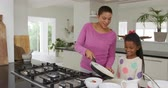 preparing : Front view of a smiling African American woman and her young daughter at home in the kitchen making food, the mother serving to a plate from a frying pan while her daughter watches, slow motion