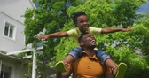 arms outstretched : Front view of a smiling African American man standing in the garden with his young son sitting on his shoulders, holding his ankles and turning around, slow motion