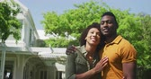 sarılma : Portrait of a smiling African American couple in the garden, embracing in the sun and smiling to camera, slow motion
