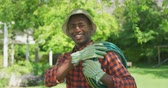 hosepipe : Portrait of an African American man standing in a cgaden wearing a hat and gardeing gloves, carrying a hose on his shoulder and smiling to camera, slow motion