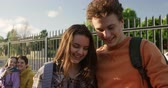 schoolplein : Front view of a Caucasian teenage girl and boy embracing and smiling while the boy takes a selfie of them with a smartphone in their school grounds, another teenage couple sitting in the background, slow motion Stockvideo