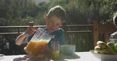 krug : Front view of a Caucasian boy at home, sitting outside on a terrace at a table for breakfast in the sun, pouring a glass of orange juice from a jug, slow motion Videos