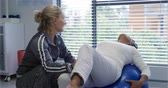 chandal : Front view of a Caucasian female physiotherapist helping a mixed race female patient exercise her leg, lying back on an exercise ball during a physiotherapy session at a hospital