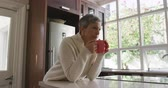 bejaardentehuis : Side view of a senior Caucasian woman with short grey hair in her kitchen at home sitting at the worktop by the window, drinking a cup of coffee, holding it with both hands, slow motion