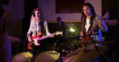 basgitaar : Over the shoulder view of a drummer playing with a Caucasian female singer guitarist with blonde curly hair and a mixed race male bass guitarist with dreadlocks, wearing headphones and performing together during a session at a recording studio. Musicians  Stockvideo