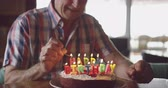 várakozás : Front view of a senior Caucasian man at home, sitting at the dining table lighting candles on a birthday cake with a match and smiling, slow motion