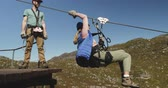 postroj : Side view of a young Caucasian woman zip lining on a sunny day in mountains while a young Caucasian man is helping her and then watching her ride, slow motion. Adventure Vacation in South Africa