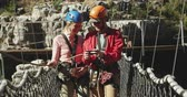 postroj : Front view of young Caucasian couple walking in zip lining equipment, man using a smartphone on a sunny day in mountains, slow motion. Adventure Vacation in South Africa