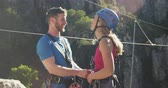 postroj : Side view of young Caucasian couple in zip lining equipment, checking harness, talking and smiling on a sunny day in mountains, slow motion. Adventure Vacation in South Africa