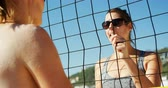 siatkówka : Female vollleyball players interacting with each other at beach 4k