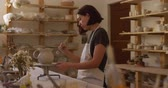cruche : Side view of a young Caucasian female potter with dark hair in a bob hairstyle wearing an apron, standing at a work table turning a jug on a banding wheel and brushing it with glaze in a pottery studio, with pots on shelves in the background, slow motion Vidéos Libres De Droits