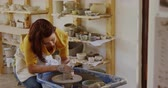 seramik : Front view of a young Caucasian female potter with auburn hair in a bob hairstyle wearing an apron, sitting at a potters wheel, turning a piece of clay and shaping it with her hands in a pottery studio, with shelves and pots in the background