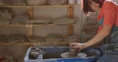 crafting : Side view of a young Caucasian female potter with auburn hair in a bob hairstyle wearing an apron, sitting at a potters wheel, turning a pot and shaping it in a pottery studio