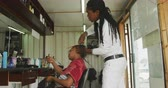 heup : Side view of an African male hairdresser in a township hair salon, adding hair extensions for an African female client, slow motion Stockvideo