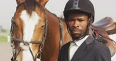 tacha : Portrait of a smartly dressed African American man wearing a riding hat, standing with his chestnut Dressage horse in a paddock, looking to camera, slow motion