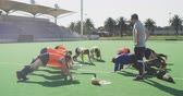 ısınma : Side view of a Caucasian male hockey coach standing and watching a team of teenage Caucasian female hockey players on all fours, exercising and stretching on the pitch before playing hockey, slow motion Stok Video
